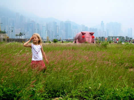 A giant, inflated suckling pig lurks in the grass.