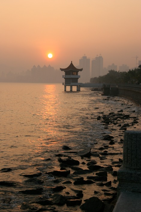 "The Zhuhai coastline in 2004. Please note that the ""romantic"" Chinese building is a guard tower and that the sunset is made brilliant orange due to heavy air pollution.  (photo by my mom, Linda Brown)"