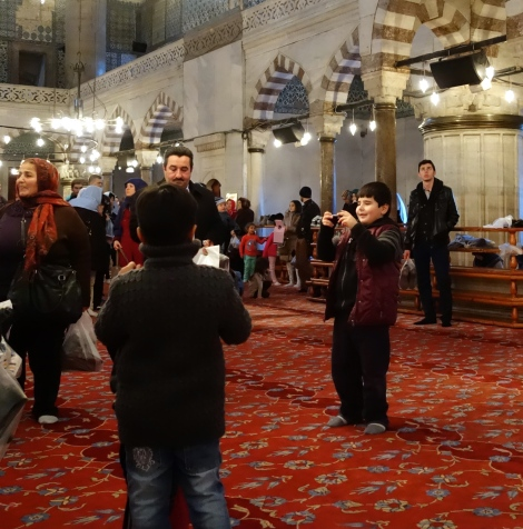 Boy taking family picture in Blue Mosque