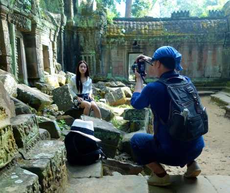 This photographer carefully posed his model, clad in high heels, all around Ta Prohm. Sometimes she posed with a white hat. Pouting was required.